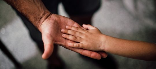 Childs hand resting in adults hand