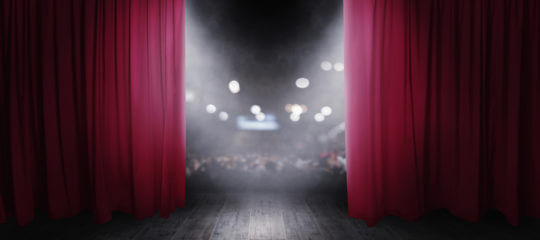 Red curtains at theatre partially open