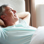 Older smiling man waking up in bed