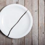 broken porcelain plate on wooden table